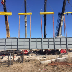 Four large cranes lifting metal barrier