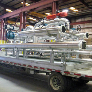 Trailer with large sections of metal pipe inside facility